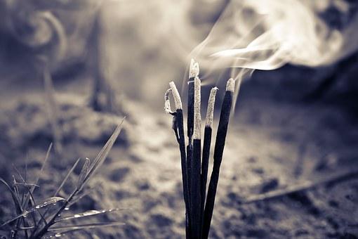 A poem by Tricia McCallum April 2, 2020. .Incense sticks emitting smoke.